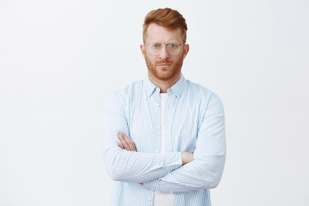 Empresário rico de aparência séria de camiseta e óculos, carrancudo, parecendo rígido com expressão calma e determinada, cruzando as mãos no peito, ouvindo atentamente durante o negócio