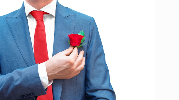 Empresário romântico no terno azul, gravata vermelha, camisa branca com rosa vermelha no bolso isolado. copie o espaço. código de vestimenta real do cavalheiro.