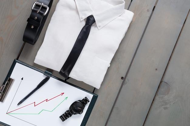 Empresário, roupa de trabalho em fundo cinza de madeira. camisa branca com gravata preta, cinto, prancheta. de volta ao trabalho. conjunto de moda e acessórios do homem. copie o espaço, moldura.