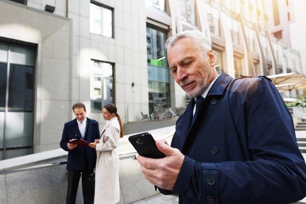 Empresário saindo do escritório com o smartphone na mão