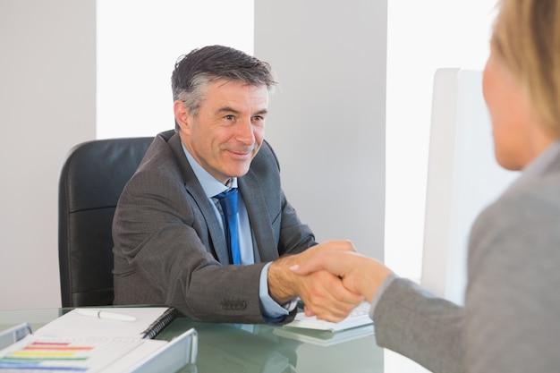 Empresário satisfeito, apertando a mão de um entrevistado