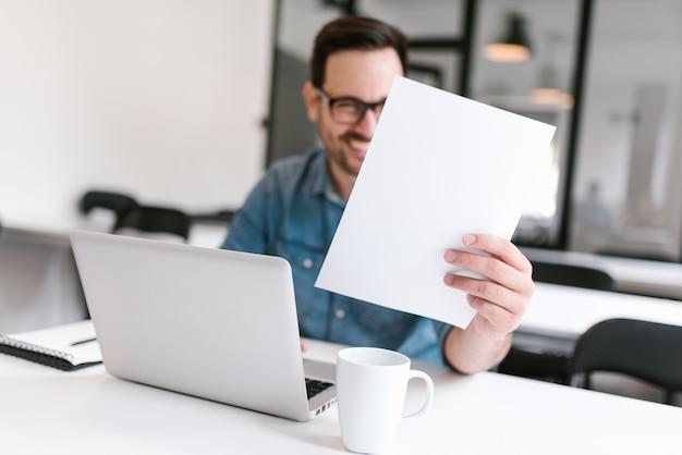 Empresário satisfeito lendo alguns documentos.
