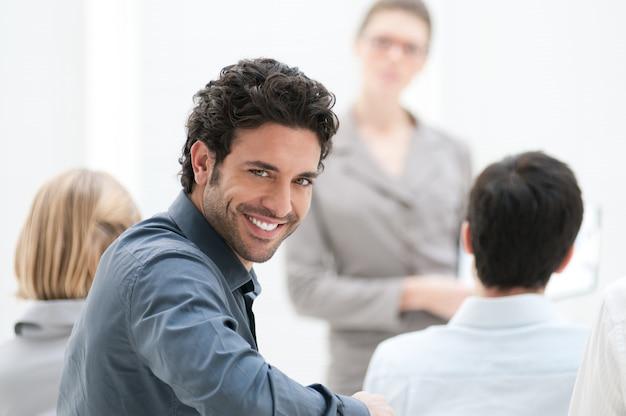 Empresário satisfeito olhando para a câmera durante uma conferência de negócios