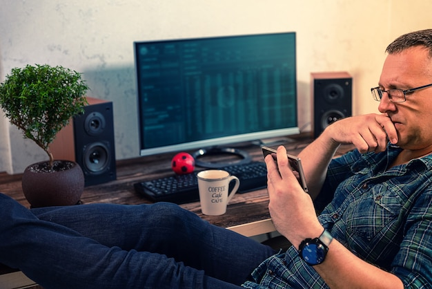 Empresário se concentrando em ler seu telefone celular enquanto relaxa em sua cadeira com os pés para cima sobre a mesa de seu escritório