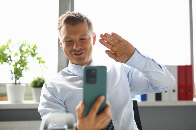 Empresário se senta no local de trabalho e acena com a mão para o smartphone em saudação. comunicação empresarial online por conceito de videochamada