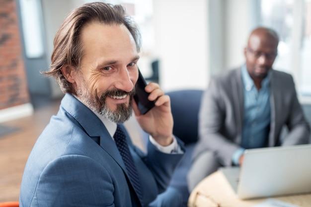 Empresário se sentindo feliz. homem de negócios de olhos escuros feliz ao receber uma ligação da esposa enquanto trabalhava