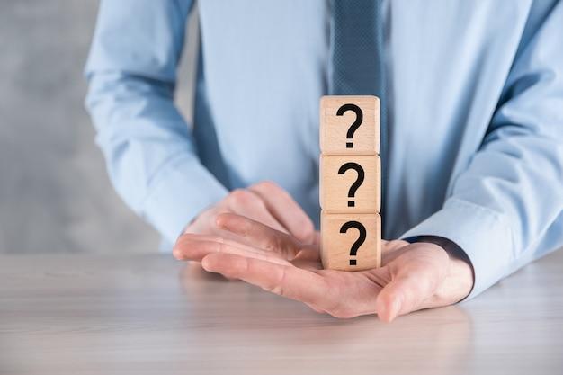 Empresário segura e coloca a forma de bloco de cubo de madeira com pontos de interrogação na mesa cinza