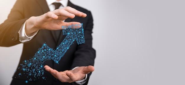 Empresário segura gráfico, seta de ícone de crescimento positivo. apontando para o gráfico de negócios criativos com setas para cima. conceito de crescimento financeiro, de negócios.