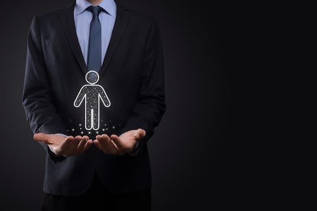 Empresário segura ícone de pessoa homem em superfície de tom escuro