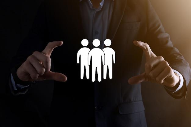 Empresário segura ícone do trabalho em equipe. construindo uma equipe forte. ícone de pessoas. recursos humanos e conceito de gestão. redes sociais, conceito de centro de avaliação, auditoria pessoal ou conceito de crm.