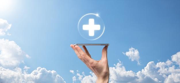 Empresário segura ícones de conexão de rede virtuais e médicos. a pandemia covid-19 desperta a consciência das pessoas e difunde a atenção sobre os cuidados de saúde.