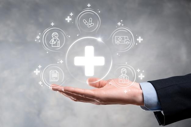 Empresário segura ícones de conexão de rede virtuais e médicos. a pandemia de covid-19 desenvolve a conscientização das pessoas e espalha a atenção sobre seus cuidados de saúde. médico, documento, medicamento, ambulância, ícone do paciente.
