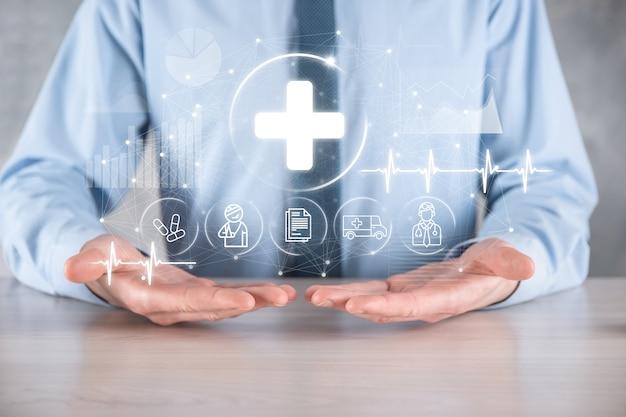 Empresário segura ícones de conexão de rede virtuais e médicos. a pandemia de covid-19 desenvolve a conscientização das pessoas e espalha a atenção sobre seus cuidados de saúde. médico, documento, medicamento, ambulância, ícone do paciente. Foto Premium
