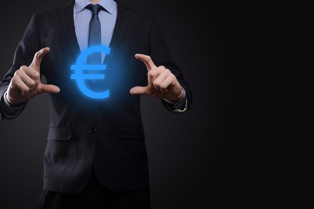 Empresário segura ícones de moeda de dinheiro eur ou euro em fundo de tom escuro. conceito de dinheiro crescente para finanças e investimentos empresariais.