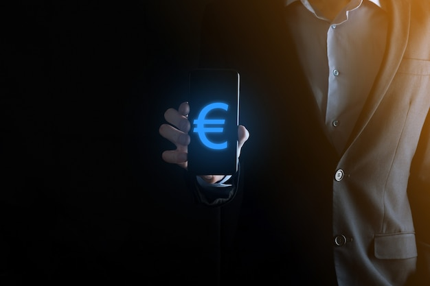 Empresário segura ícones de moeda de dinheiro eur ou euro na superfície de tom escuro