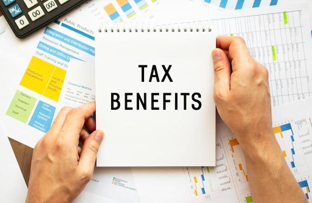 Empresário segura o bloco de notas com benefícios fiscais de texto. gráficos financeiros na área de trabalho. conceito financeiro e de negócios.