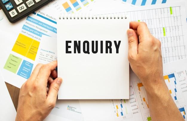 Empresário segura o bloco de notas com o texto inquérito. gráficos financeiros na área de trabalho. conceito financeiro e de negócios.
