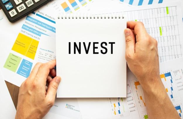 Empresário segura o bloco de notas com o texto investir. gráficos financeiros no desktop