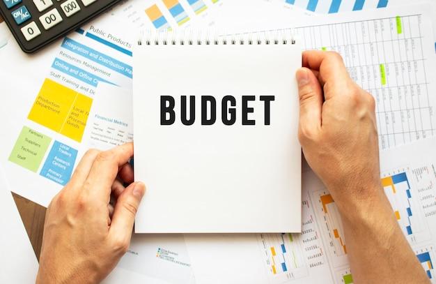 Empresário segura o bloco de notas com o texto orçamento. gráficos financeiros na área de trabalho.