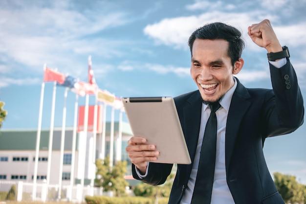 Empresário segura tablet feliz sucesso no mercado de ações de comércio de investimento empresarial