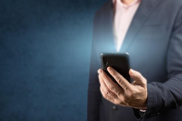 Empresário segura um telefone celular.