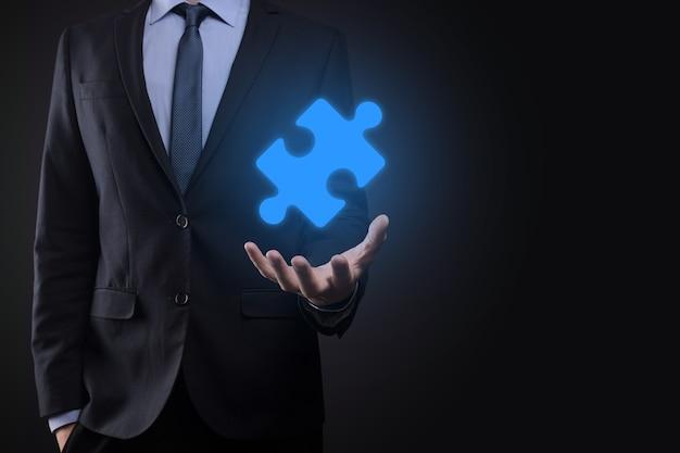 Empresário segura uma peça do quebra-cabeça nas mãos