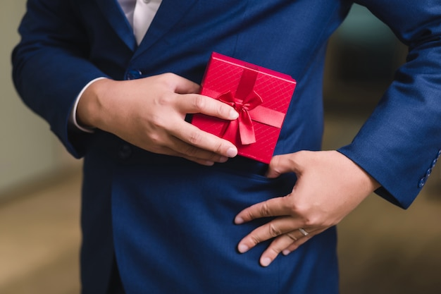 Empresário, segurando a caixa de presente vermelha