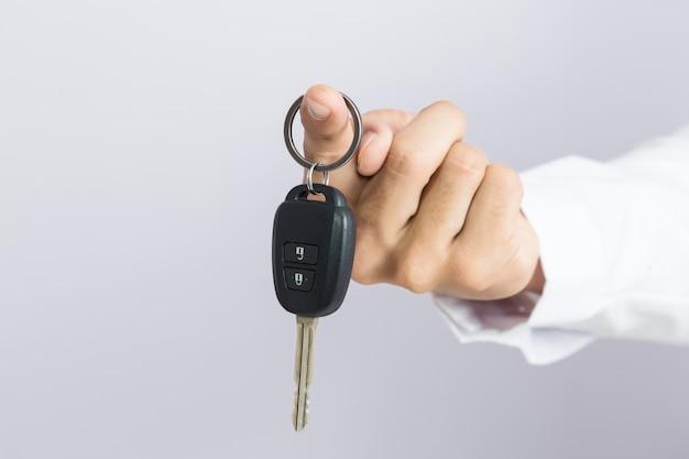 Empresário segurando a chave do carro, fundo isolado
