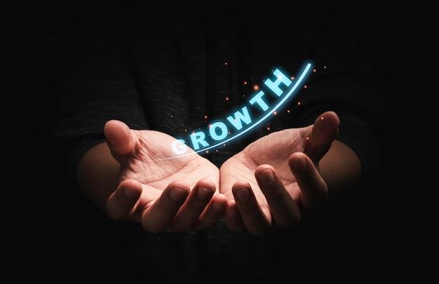 Empresário, segurando a formulação de crescimento com a seta para o lucro empresarial e o conceito de aumento de investimento.