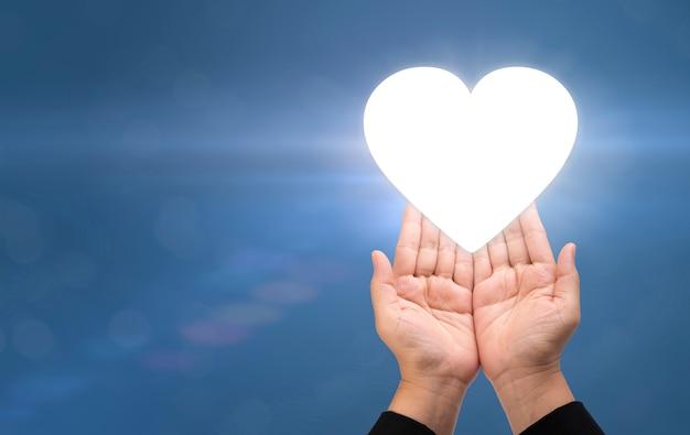 Empresário segurando a imagem digital do coração com cuidado conceito para serviços inteligentes pós-venda