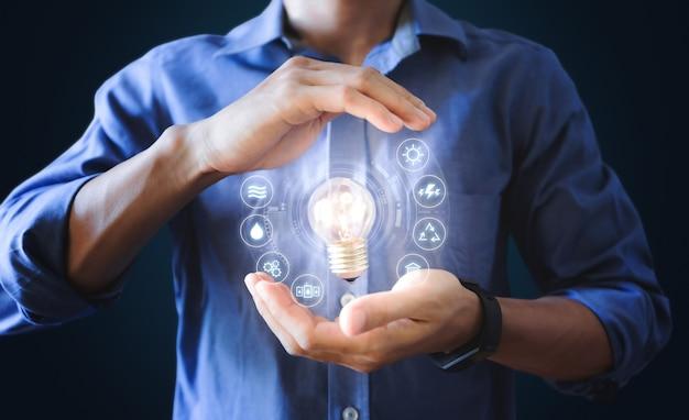 Empresário, segurando a lâmpada brilhante com ícone de recursos de energia