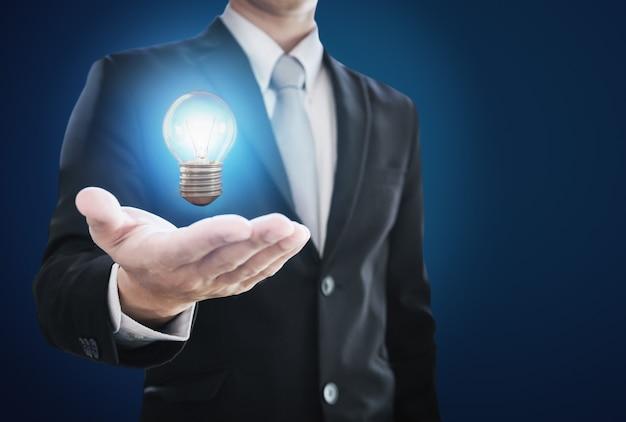 Empresário, segurando a lâmpada incandescente por lado