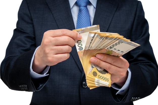 Empresário segurando a moeda coreana na mão.