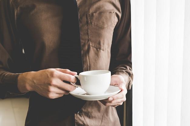 Empresário segurando a xícara de café na janela. idéia de inicialização de negócios criativos.
