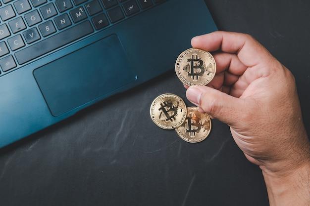 Empresário segurando bitcoin e laptop