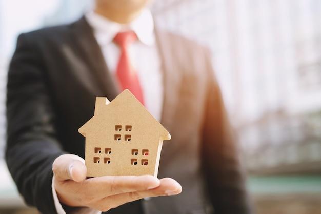 Empresário segurando casa modelo
