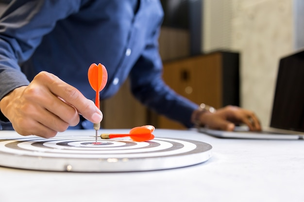 Empresário segurando dardos apontando para o centro do alvo