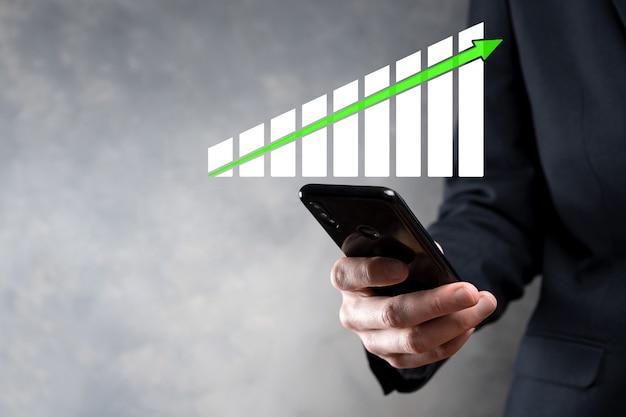 Empresário segurando gráfico de crescimento e aumento de indicadores positivos de gráfico em seu negócio. investimento acima do conceito de análise de dados de vendas e estratégia econômica e planejamento marketing digital e estoque