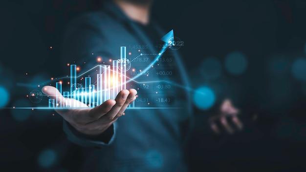 Empresário segurando gráfico técnico virtual e gráfico para análise, mercado de ações e conceito de comerciante.