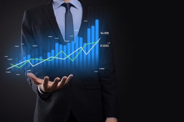 Empresário segurando gráficos holográficos e estatísticas do mercado de ações obtém lucros