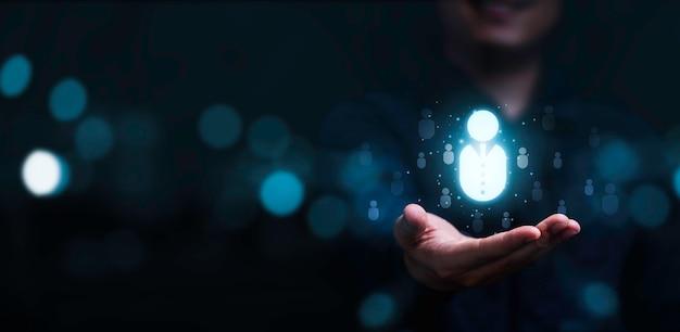 Empresário segurando ícone humano virtual para grupo de clientes de foco ou recrutamento humano e conceito de desenvolvimento.