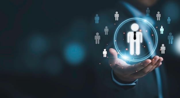Empresário segurando infográfico virtual com ícones humanos para o conceito de desenvolvimento e recrutamento humano.