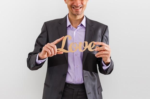 Empresário segurando letras de amor em um fundo isolado - gestão de relacionamento com o cliente