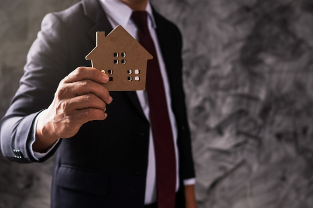 Empresário segurando modelo de casa