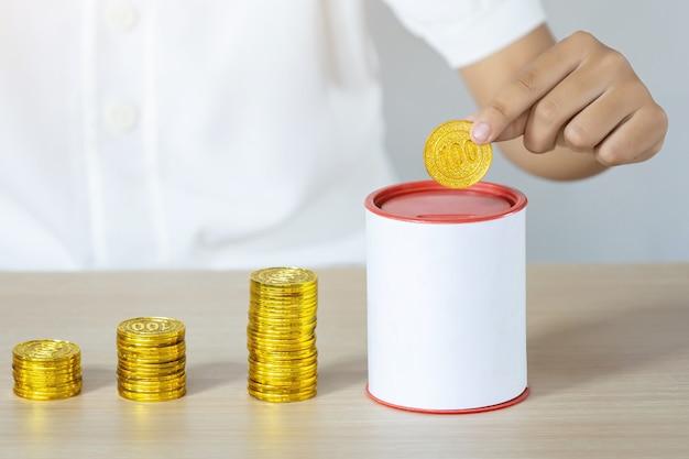 Empresário segurando moedas de ouro, colocando no banco de moedas. conceito de economia de dinheiro para contabilidade financeira