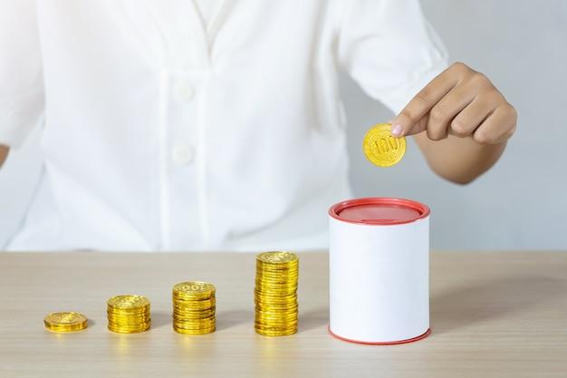 Empresário segurando moedas de ouro e colocando no banco de moedas