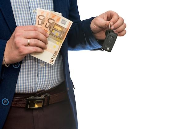 Empresário segurando notas de euro e as chaves do carro isoladas. compre ou alugue um carro conceito