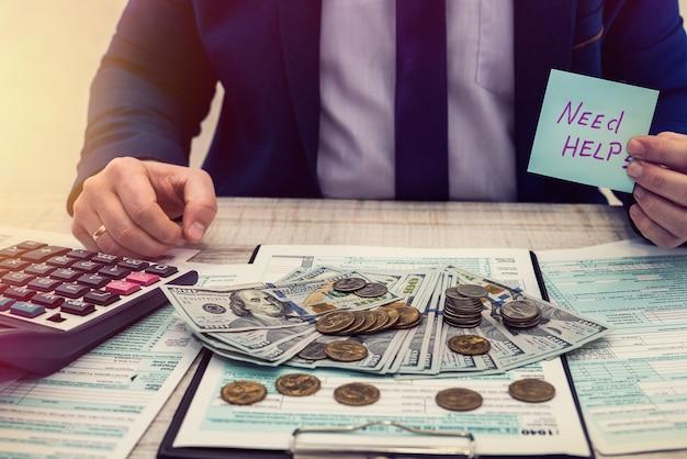 Empresário segurando o adesivo com a inscrição precisa de ajuda para preencher o formulário fiscal 1040 dos eua e contando dinheiro. conceito de preenchimento de mão de escritório de renda de negócios nos estados unidos