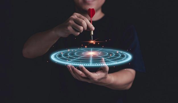 Empresário, segurando o alvo de dardos azul virtual com seta vermelha do dardo para o conceito de destino de objetivos de negócios de configuração.