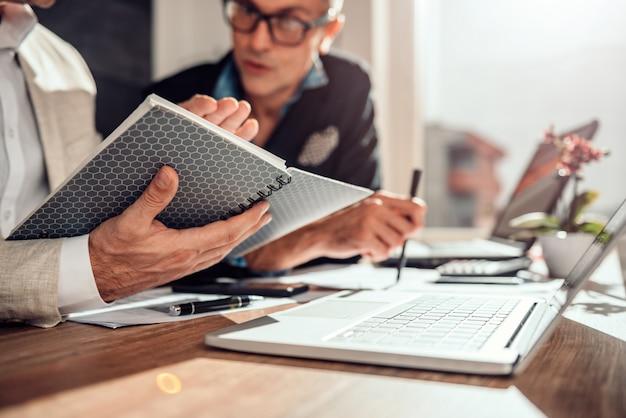 Empresário, segurando o bloco de notas durante uma reunião